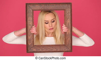 Seductive woman framing her face in a frame