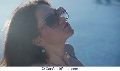 """Seductive woman in sunglasses tanning in sunlight at resort"""