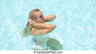 Seductive Woman in the Pool Holding her Neck