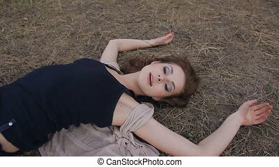 Seductive woman lying on the grass smiling and posing