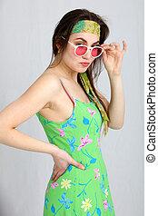 Seductive woman peering over her sunglasses
