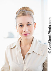 Seductive young blonde businesswoman looking at camera
