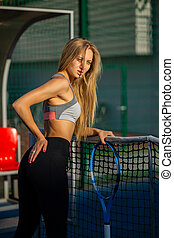 Seductive young fitness model with perfect long hair posing with a tennis racket at the court