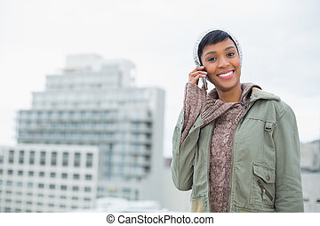 Seductive young model in winter clothes calling someone with her mobile phone outside on a cloudy day