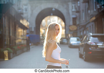Seductive young model with long hair holding glasses, posing at the passage in rays of sun. Copy space