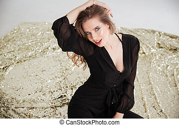 Seductive young woman in black dress sitting and posing