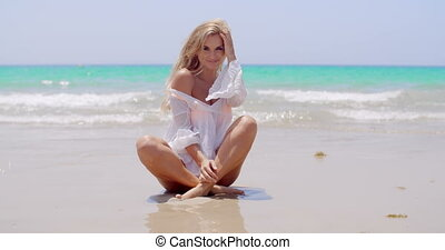 Seductive Young Woman Sitting on the Beach Sand