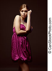 Seductive young woman wearing pink dress