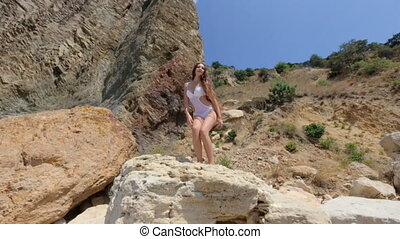 Seductive young woman with long hair in a white bathing suit seductively moves standing on a rock