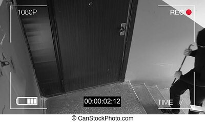 See CCTV as a burglar breaking in through the door with a...