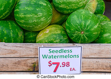 Seedless watermelons in wooden crate with price tag label at farmer market in USA