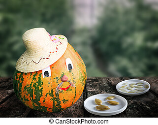 Seeds and fruits of a pumpkin on blurred background of the greenhouse.
