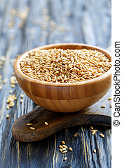 Seeds of oats in a wooden bowl.