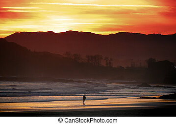 Silhouette of solitary man meditating at dawn in the beach