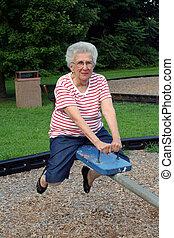 Seesaw Grandma 5 - Senior citizen woman on playground...