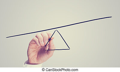 Seesaw showing an imbalance - Male hand drawing a seesaw...