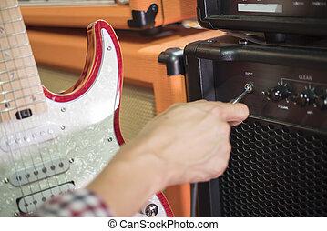 segurando, amplificador, cima, mão, guitarra, macaco, fechado, conecte tomada