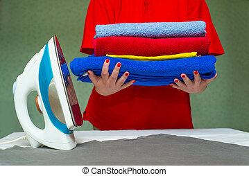 segurando, coloridos, mulher, pilha, ferro, mãos, roupas