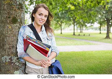 segurando, dela, árvore, livros, estudante, inclinar-se, sorrindo