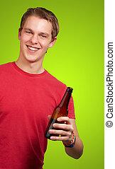 segurando, sobre, jovem, cerveja, experiência verde, homem