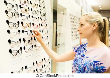 sehen sorgfalt, -, junge frau, wählen neuen gläsern, in, optiker, kaufmannsladen