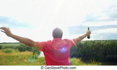 seine, ungefähr, gestein, junger, Regen, Arme, bier, Draußen, hebt, hintergrund, Sonnenlicht, spinnen, Mann, lacht