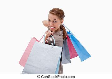 seitenansicht, von, lächelnde frau, mit, einkaufstüten