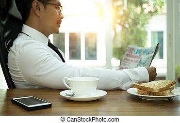 Selected focus coffee mug businessman having breakfast and reading a newspaper with cell pone