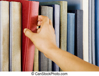 Selecting a book - Image of a hand selecting a red book from...