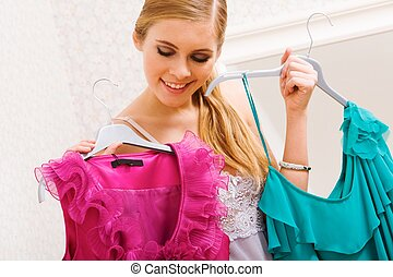 Selecting clothes - Image of pretty female looking at smart...