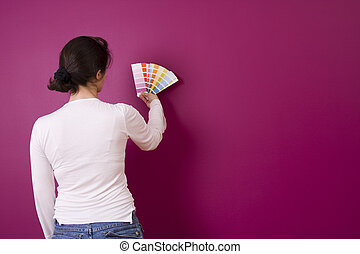 Selecting color - woman select a color to paint her wall (...