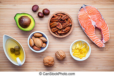 Selection food sources of omega 3 and unsaturated fats. Super food high vitamin e and dietary fiber for healthy food. Almond ,pecan ,hazelnuts, walnuts ,olive oil ,fish oil ,salmon on cutting board.