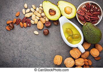 Selection food sources of omega 3 and unsaturated fats. Superfood high vitamin e and dietary fiber for healthy food. Almond ,pecan, hazelnuts, walnuts, olive oil, fish oil and salmon on stone background.