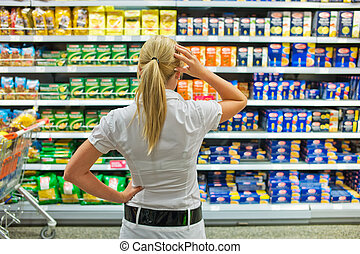 selection in a supermarket - a woman is overwhelmed by the...