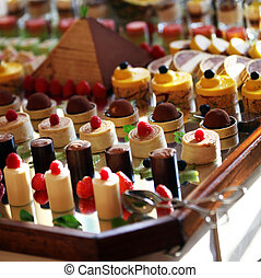 Selection of decorative desserts on a buffet table at a ...