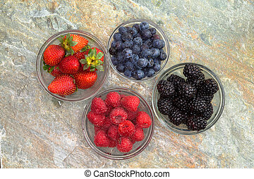 Selection of different fresh berries in glass jars
