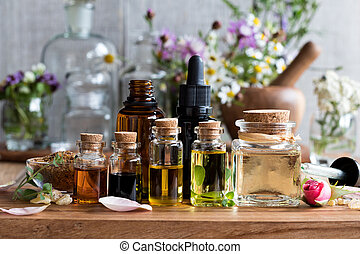 Selection of essential oils with herbs and flowers - ...