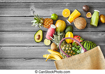 Selection of fresh tropical fruit and smoothies or juice in glass bottles spilling from a reusable textile shopping bag onto a wood background in a concept of a healthy diet and nutrition