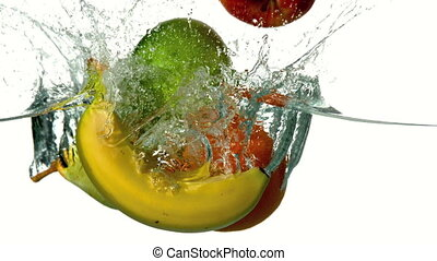 Selection of fruit plunging into water on white background...