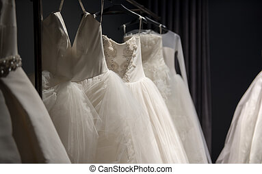Selection of handmade white wedding gowns hanging on a rail...