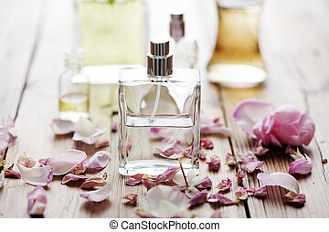 selection of perfume bottles surrounded by flower petals