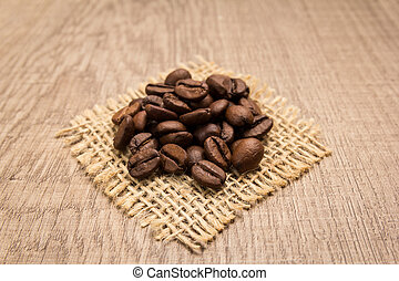 coffee beans seed. Grains on square cutout of jute. Wooden table. Selective focus.