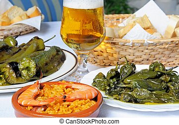 Tapas selection of Padron peppers, Deep fried pointed peppers, seafood and pork paella, Costa del Sol, Malaga Province, Andalucia, Spain, Western Europe.