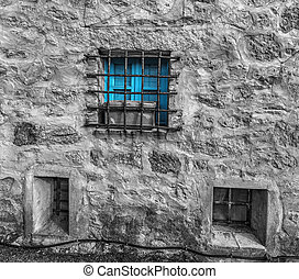 selective desaturation of a blue window in a rustic wall in...