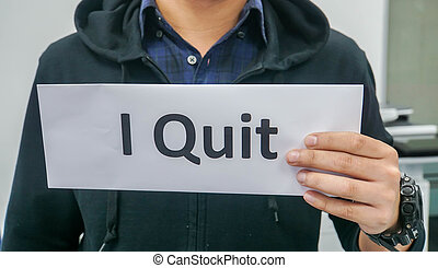 selective focus close up man in black jacket holds paper of I quit for resignation in office