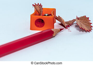 Color pencil with sharpener shavings on white background