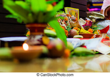 Selective focus. Diwali puja or Laxmi puja set up at home. Oil lamp or diya with crackers, sweet, dry fruits, indian currency, flowers and statue of Goddess Laxmi on a festival Diwali night.