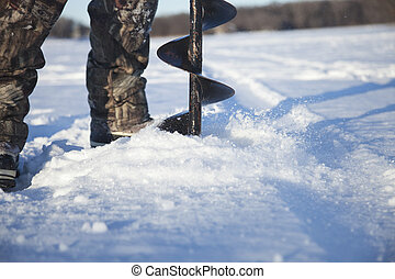 Selective focus fisherman drilling hole in ice with auger -...