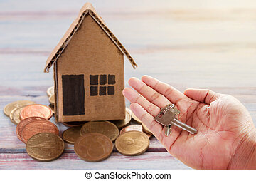 Human hand holding key of paper house toy or cardboard house