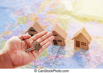 Human hand holding key of paper house toy or cardboard house on world map with morning sunlight.